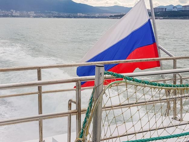 Russische driekleurige vlag op een schip, tegen de achtergrond van de zee en de kustlijn met een kuststad, dageraad, zomer.