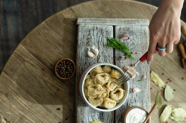 Russische dumplings met zure room, dille en knoflook op een houten dienblad