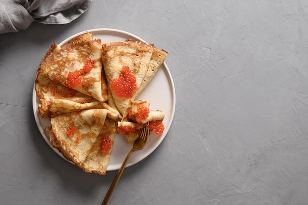 Russische dunne pannenkoeken of blini met rode kaviaar op grijs
