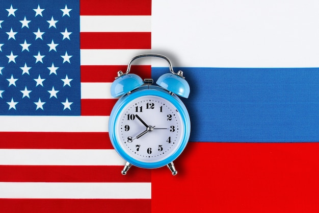 Russische en amerikaanse vlaggen en de klok als symbool van politieke betrekkingen. creatief bovenaanzicht plat leggen van de wekker van de vlag van rusland en de vs. concept van confrontatie tussen de vs en rusland