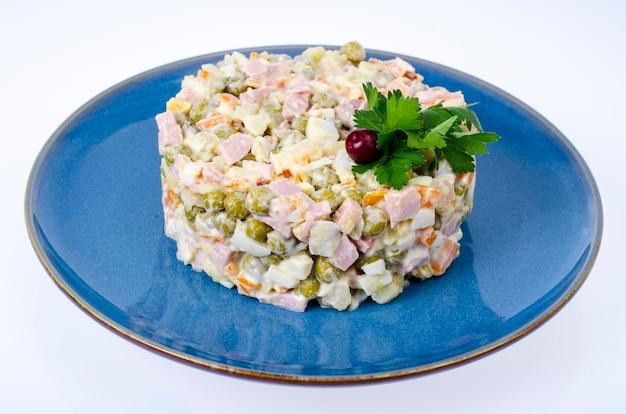 Russische groentesalade met erwten en mayonaise op blauw bord. studio foto