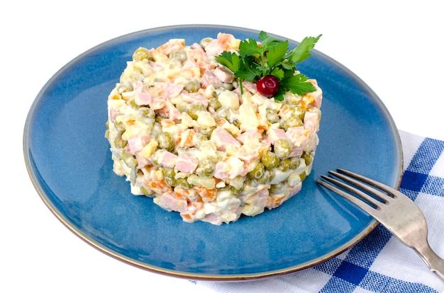 Russische groentesalade met erwten en mayonaise op blauw bord.