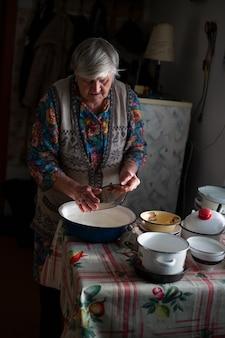 Russische grootmoeder, wast de afwas, in een bassin in het dorp.