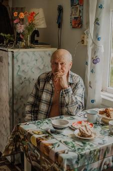 Russische grootvader zit in een shirt aan de tafel
