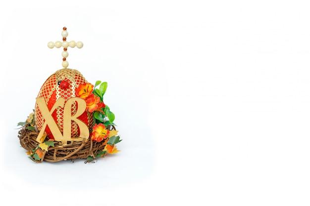 Russische handgemaakte paasei souvenir versierd met een kruis en afkorting letters xb voor christus is toegenomen. geïsoleerd op witte achtergrond happy easter concept. ruimte voor tekst kopiëren
