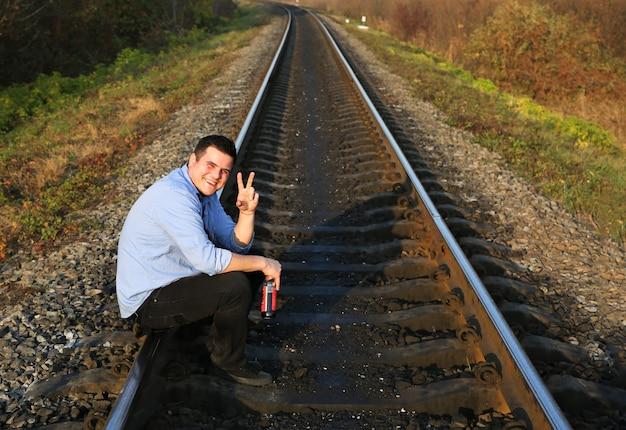Russische man met alcohol op spoorlijnen buitenshuis. eenzaam persoon. zelfmoordconcept. depressie ziekte. een glimlach dwingen alcoholist.