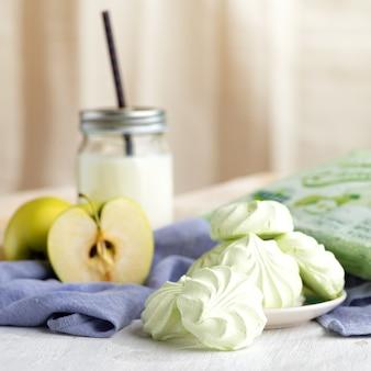 Russische marshmallow op de plaat, appels en thee op tafel. het stilleven, selectieve aandacht. verticaal, 1: 1