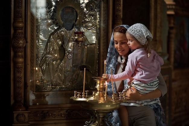 Russische mooie vrouw in een sjaal en met rood haar met een klein meisje en steekt een kaars aan voor een pictogram in de russisch-orthodoxe kerk.