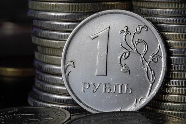 Russische munt van 1 roebel (keerzijde) tegen de achtergrond van andere munten die in kolommen zijn gevouwen.
