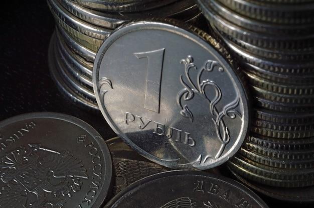 Russische munt van 1 roebel (omgekeerd) tegen de achtergrond van andere munten gevouwen in kolommen.