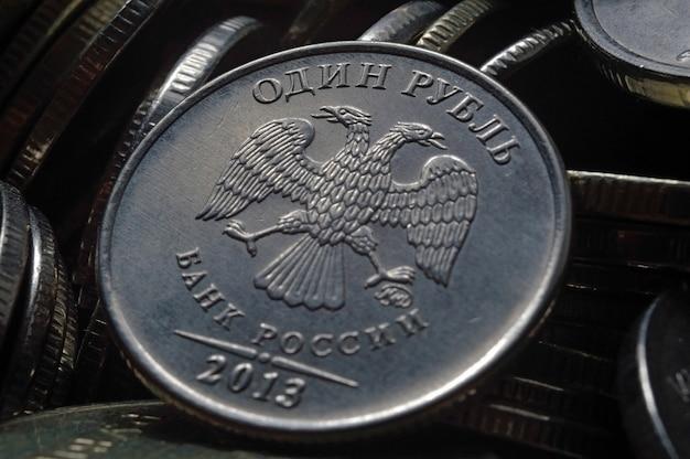 Russische munt van 1 roebel (voorzijde) tegen de achtergrond van andere russische roebels van verschillende denominaties. macro.