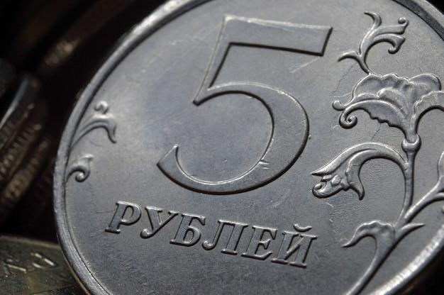 Russische munt van 5 roebel denominatie (omgekeerde) tegen de achtergrond van andere munten. macro. Premium Foto