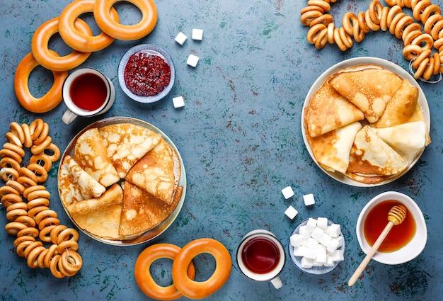 Russische pannenkoekblini met frambozenjam, honing, verse room en rode kaviaar, suikerklontjes, kwark, bubliks op donker