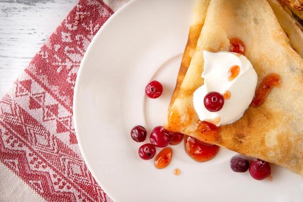 Russische pannenkoeken met zure room, bessen, veenbessen en jam op een bord, thee, jam op een handdoek met een rood patroon op een wit oppervlak, bovenaanzicht,