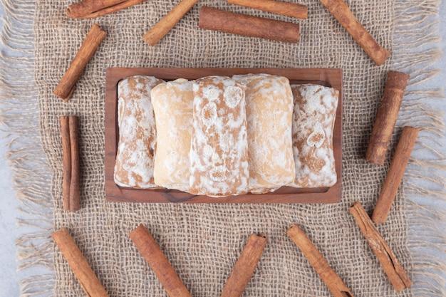 Russische pryanik-koekjes op een klein dienblad, omringd met kaneelstokjes op textieltafel.