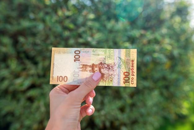 Russische roebel in vrouwelijke hand. honderd zeldzaam inbaar bankbiljet. contant geld.