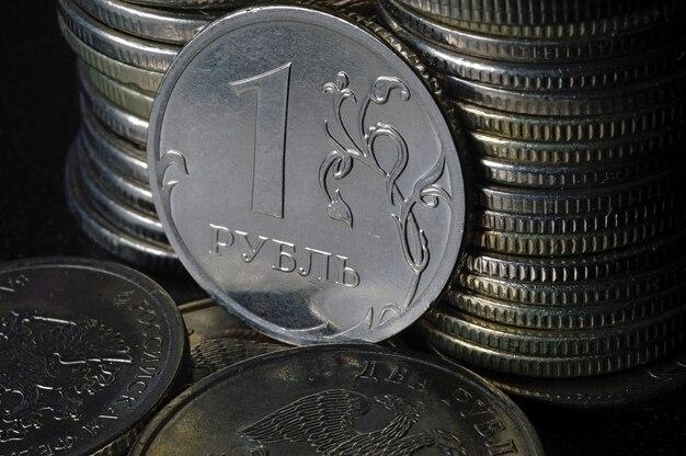 Russische roebel munt tegen de achtergrond van andere munten gevouwen in kolommen