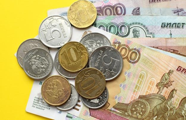 Russische roebels op een gele achtergrond. bankbiljetten en verschillende munten.