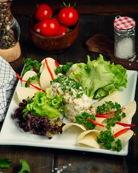 Russische salade gegarneerd met kruiden
