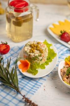 Russische salade olivie, stolichni met gekookte groenten, vlees en gegraneerde beens