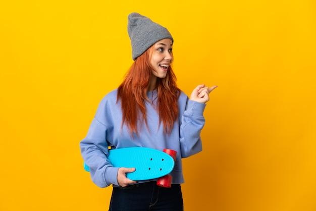 Russische skater vrouw geïsoleerd op geel van plan om de oplossing te realiseren terwijl ze een vinger opheft