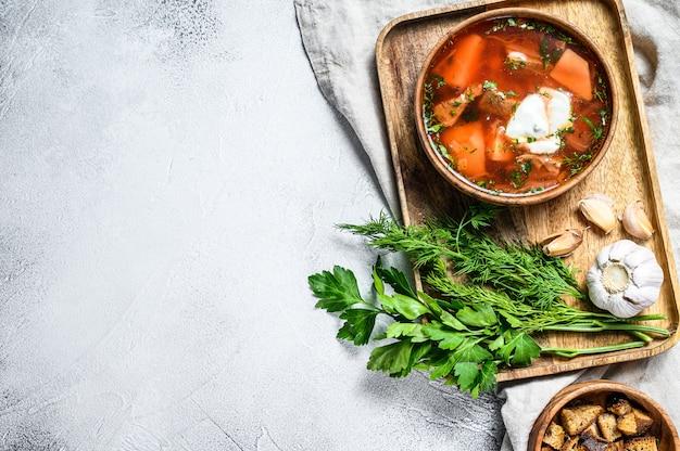 Russische specialiteit borsch-soep met rode biet en zure room. grijze achtergrond. bovenaanzicht. ruimte voor tekst