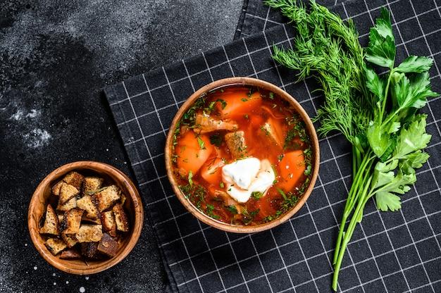 Russische specialiteit borsch-soep met rode biet en zure room. zwarte achtergrond. bovenaanzicht