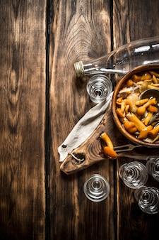 Russische stijl. wodka met ingelegde champignons. op houten achtergrond.