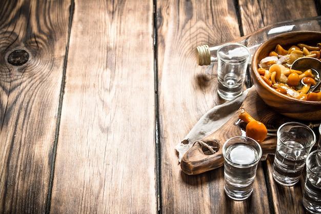 Russische stijl wodka met ingelegde paddestoelen op houten achtergrond
