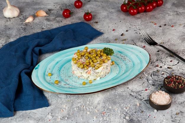 Russische traditionele salade olivier, grijze achtergrond