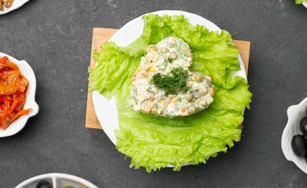 Russische traditionele salade stolichni met sla. bovenaanzicht