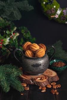 Russische traditionele zelfgemaakte koekjes noten - oreshki met gecondenseerde melk op een vintage pot op een houten standaard, omringd door vuren takken en verspreide noten.