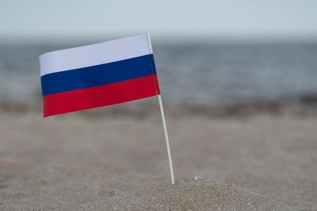 Russische vlag op het strand. zomervakantie op zee. driekleurige vlag van wit blauw rood.