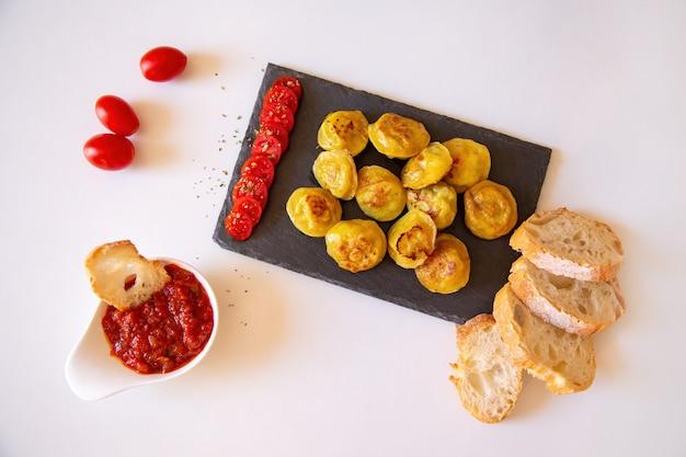 Russische voedselpelmeni, gebraden vleesbollen op steenplaat, met tomates, brood en rode saus. bovenaanzicht, platliggend.