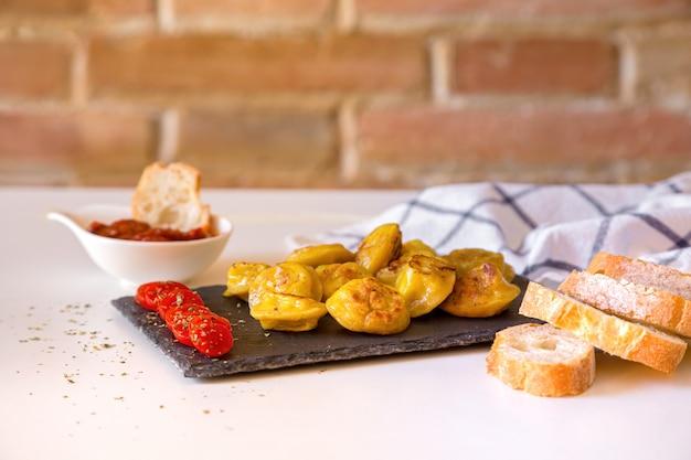Russische voedselpelmeni, gebraden vleesbollen op steenplaat, met tomates, brood en rode saus.