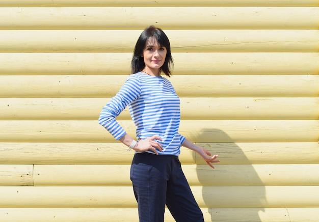 Russische vrouw die zich tegen houten gele muur bevindt
