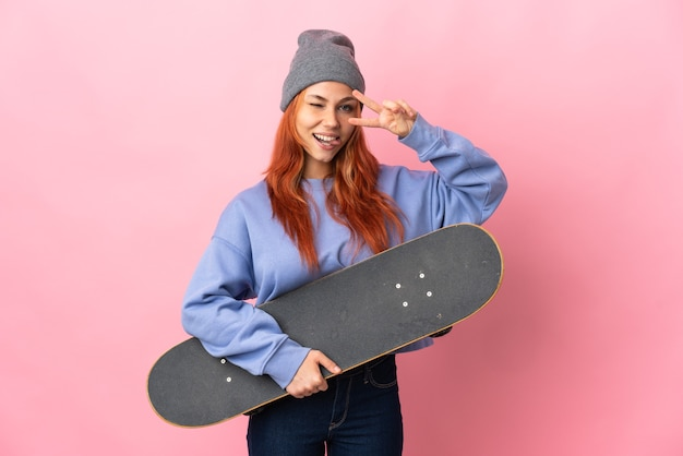 Russische vrouw geïsoleerd op roze met een skate met gelukkige uitdrukking