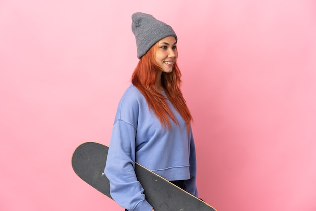 Russische vrouw geïsoleerd op roze met een skate