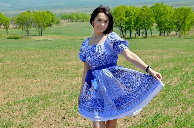 Russische vrouw, gekleed in blauwe jurk op een groen veld.