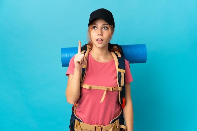 Russische wandelaar vrouw geïsoleerd op blauw denken een idee met de vinger omhoog