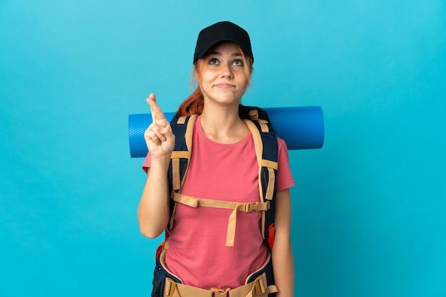Russische wandelaar vrouw geïsoleerd op blauw met vingers kruisen en het beste wensen