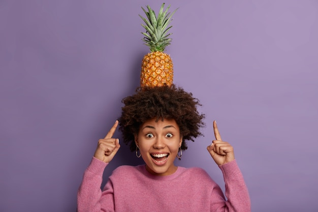 Rust en relax. kijk hoe ik kan! blij krullend etnisch meisje wijst naar rijpe ananas op het hoofd, lacht positief