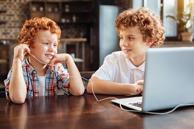Rust en sereniteit. vrolijke jongens met krullend haar die achter een laptop zitten terwijl ze allebei naar muziek luisteren in de oortelefoons en glimlachen terwijl ze genieten van de melodie.
