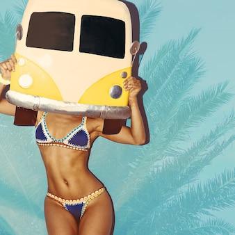 Rust en strand. meisje in modieuze zwembroek. surfende auto