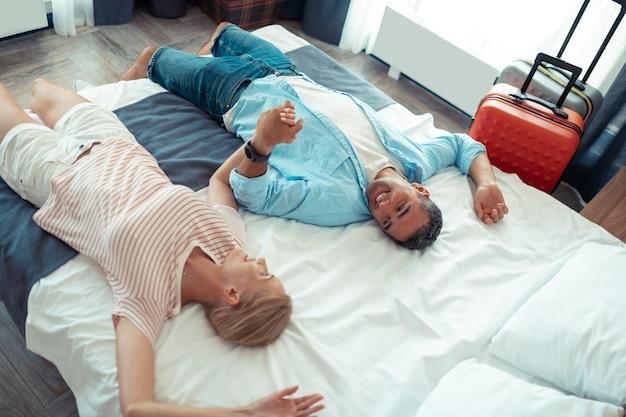 Rust hebben. gelukkige man en vrouw hand in hand op het hotelbed moe na het vliegen.