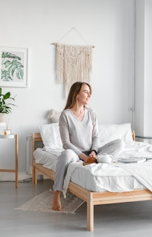 Rust na een dag hard werken. mooie jonge glimlachende bedrijfsvrouw in koffie drinken en pyjama's die weg terwijl het zitten op een bed in een witte ruimte kijken.