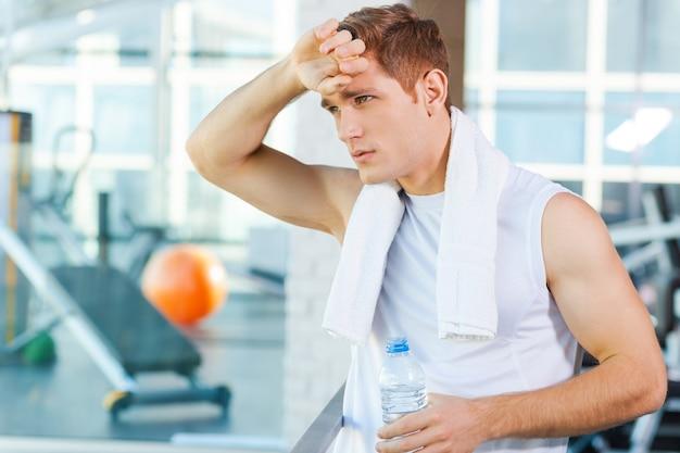 Rust na het sporten. vermoeide jongeman die een handdoek op zijn schouders draagt en zijn voorhoofd aanraakt terwijl hij in de sportschool staat