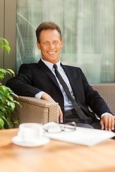 Rust nemen na een zakelijke bijeenkomst. vrolijke volwassen man in formalwear die naar de camera kijkt en glimlacht terwijl hij buiten op de stoel zit met een koffiekopje op de voorgrond