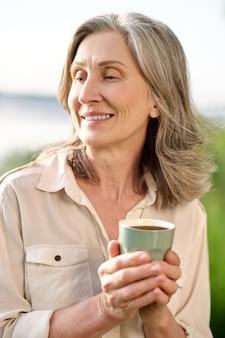 Rust. peinzende kalme vrouw van pensioengerechtigde leeftijd met koffie in de natuur op warme dag