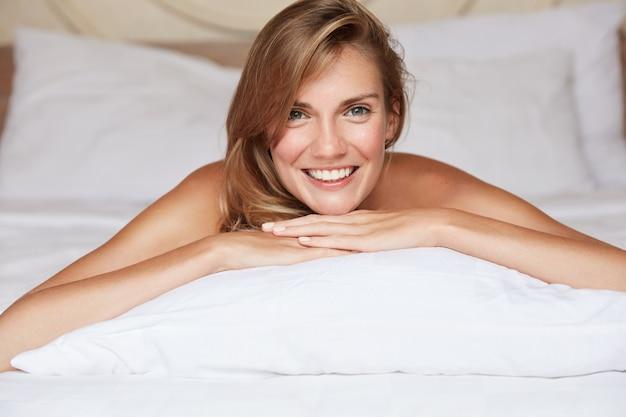 Rust-, slaap- en comfortconcept. lachende mooie ontspannen jonge vrouw met positieve uitdrukking ligt op buik op wit linnen, geniet van een rustige huiselijke sfeer in een gezellige slaapkamer of hotelkamer
